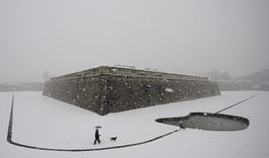 24 Hours: A couple walk in the snow with their dog at Vuelta Castillo Park, Spain
