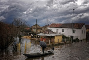 24 Hours: A local villager stands in a boat in the flooded village of Bijelo Polje