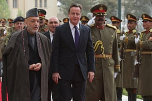 Cameron in Afghanistan : Cameron and Afghan President Hamid Karzai pass an national honor guard