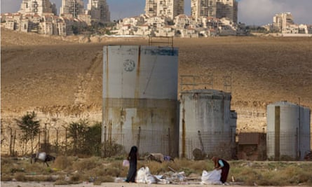 Palestinian women collect scrap timber near the Jewish West Bank settlement of Maaleh Adumim
