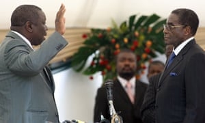 Robert Mugabe, right, swears in Morgan Tsvangirai as prime minister
