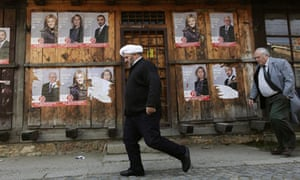 Men walks past campaign posters in Gjakova town, Kosovo, ahead of the 12 December elections