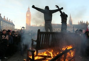 student protest update: Two demonstrators stand ontop of a bonfire in Parliament Square