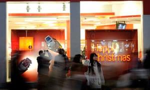 Christmas shoppers walk along Oxford Street, London.