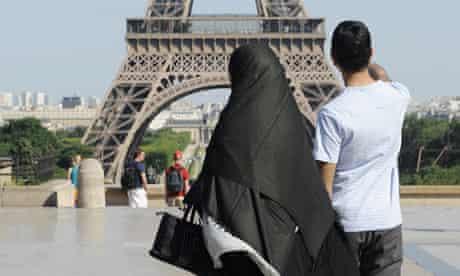 A woman wearing a niqab walks near the Eiffel Tower in Paris.