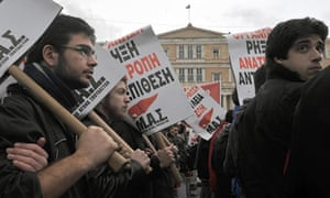 Demonstrators march in front of the Greek Parliament