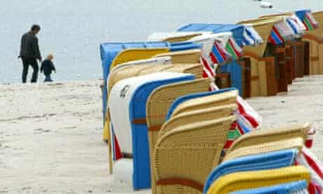 A man and a boy stroll along the beach past colourful chairs in Schilksee on the Baltic sea coast