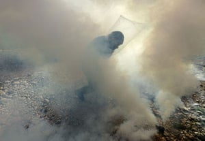 West Bank demonstration: A Palestinian protester runs to throw back a tear gas canister