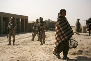 Operation Moshtarak : An Afghan boy carries his pet bird past US Marines