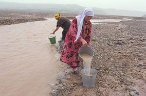 Tajikistan Climate: Bachamazor village water comittee, filling their buckets Tajikistan