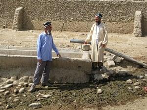 Tajikistan Climate: Two farmers standing by disused water point in Davat village Tajikistan