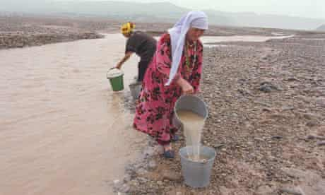 Oxfam established village water comittee, filling their buckets with river water, Tajikistan