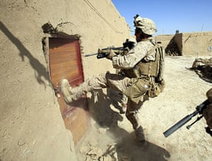 Operation Mshtarak: A US Marine breaks the door of a house to search for weapons