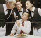 Man dining, showing portion of meat on fork to waiters and waitress