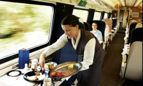 Food being served in a first-class train carriage.