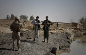 Operation Moshtarak: US Marine with NATO forces instructs Afghan men to raise clothes, Marjah