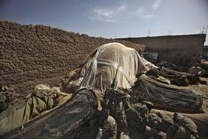 Operation Moshtarak: An US Marine sleeps outside a makeshift base in Marjah