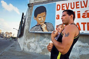 Elian Timeline: A Cuban man walks with a baby in Havana past a poster of Elian Gonzalez