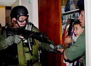 Elian Timeline: Elian Gonzalez, held by Donato Dalrymple, is taken by U.S. federal agents