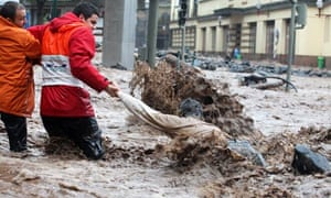 A man is helped while trying to cross a flooded street in Funchal, Madeira's capital
