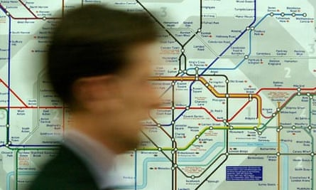 A commuter passes a map of the London Underground system at Westminster tube station