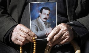 The father of Mahmoud al-Mabhouh holds a photograph of his son