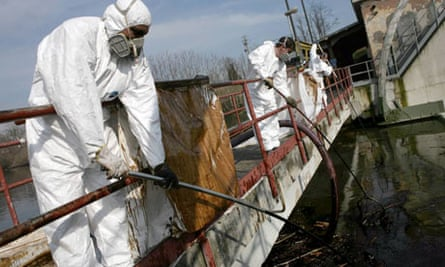Workers clean up an oil spill on the Lambro river, a tributary of the Po, near Milan.
