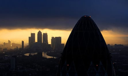 The sun rises over the City of London.