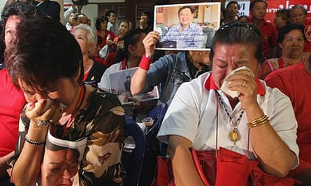 Supporters of former Thai prime minister Thaksin Shinawatra cry at the verdict to seize his frozen assets