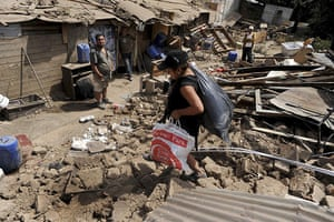 Chile Earthquake: A woman recovers belongings Santo Domingo Street in Santiago, Chile