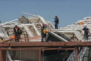 Chile Earthquake: Rescue workers inspect a damaged building in Concepcion