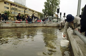 chile update: Residents draw water for daily use from a public fountain in Concepcion