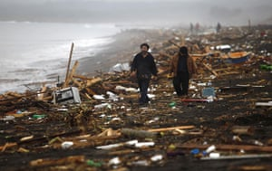 chile update: People walk along the shore after an earthquake in Pelluhue, Chile