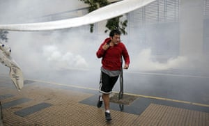 chile update: A man run away from tear gas, during looting in Concepcion, Chile