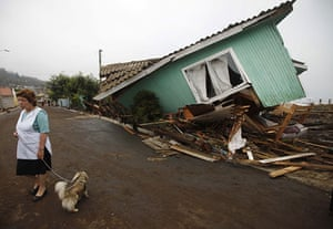 chile update: A woman stands in front of a damaged house in Pelluhue, Chile