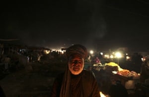 24 hours: Kabul, Afghanistan: A street vendor stands in front of a bonfire