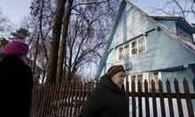 People walk past an old house at the Sokol Village, Moscow