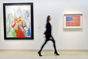 24 Hours in Pictures: A woman poses with Jasper Johns Flag and Femme et Filettes by Pablo Picasso