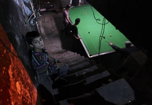 24 Hours in Pictures: Pakistani men play snooker in a club in Lahore