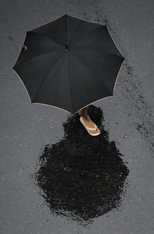 24 Hours in Pictures: A woman crosses a street under heavy rain in Buenos Aires