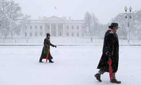 Pedestrians walk past the White House as snow continues to fall on Washington