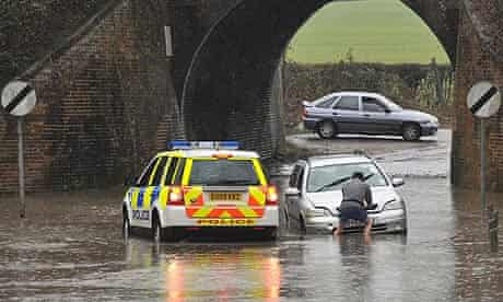 A driver is helped by police after getting stuck on a flooded road in Essex