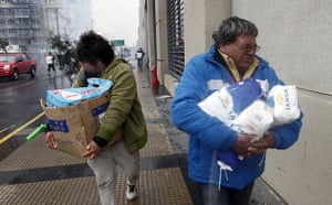 Chile earthquake: People carry goods during looting in Concepcion, Chile after an earthquake