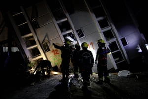 Chile earthquake: Firemen look for survivors in a building in Concepcion