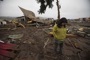 Chile earthquake: A woman stands in front of a damaged house in Pelluhue