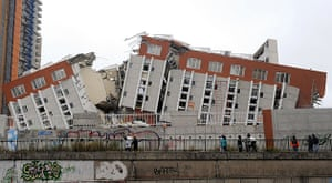 Chile earthquake: Passersby observe the remains of a destroyed building in Concepcion