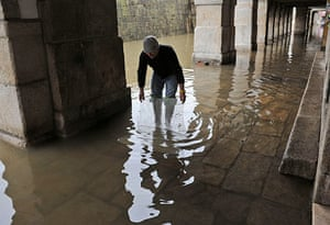 Storm damage in Europe: A Portuguese man amuses himself trying to catch fish trapped in floods