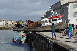 Storm damage in Europe: People look at a damaged boat in the port of Saint-Martin-de-Re