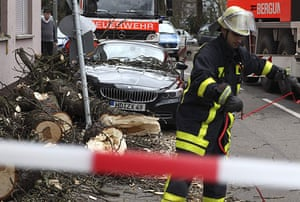 Storm damage in Europe: A fireman works next to a car damaged by a tree in Frankfurt