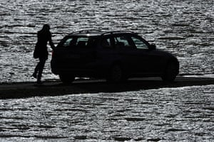 Storm damage in Europe: A woman gets into her car at a partly flooded street in Bunsendorf, Germany
